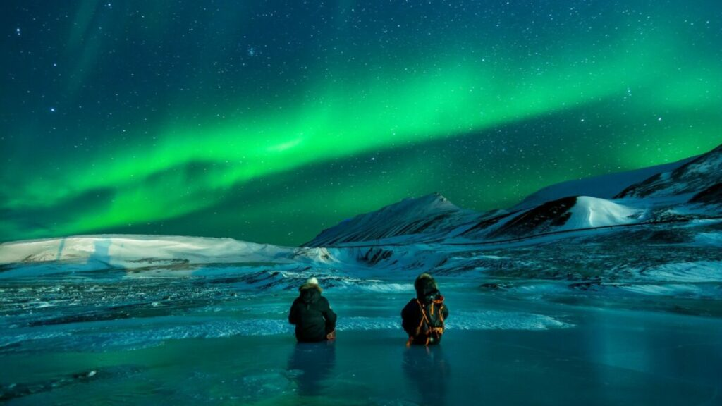 Two people in a frozen lake watching the aurora